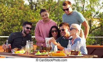 happy friends using smartphone at rooftop party - leisure...