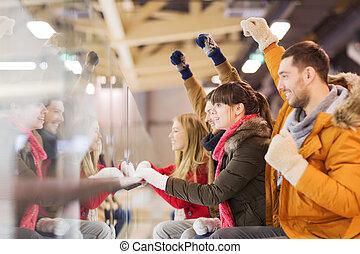 happy friends watching hockey game on skating rink - people,...