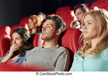 happy friends watching horror movie in theater - cinema,...