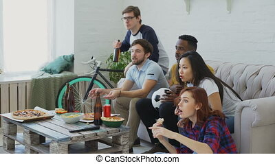 Happy friends watching sports championship on TV together at...