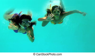 Happy friends waving at camera underwater