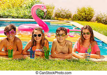 Happy friends with beverages on outdoor pool party