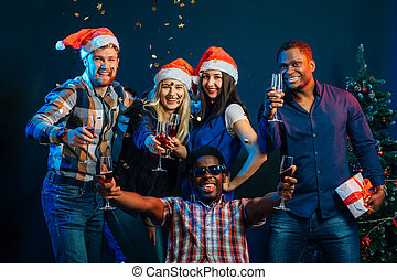 Happy friends with champagne celebrating Christmas