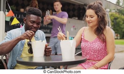 happy friends with drinks eating wok at food truck - leisure...