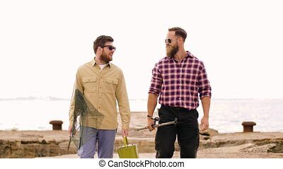 happy friends with fishing rods walking along pier - leisure...