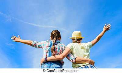 Happy friends with open arms under blue sky.  Two girls having fun - relax outdoors