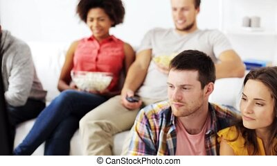 happy friends with popcorn watching tv at home - friendship,...