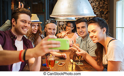 happy friends with smartphone taking selfie at bar - people...
