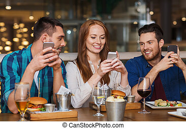 happy friends with smartphones at restaurant - leisure,...