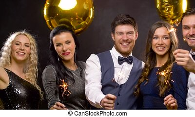 happy friends with sparklers at christmas party -...