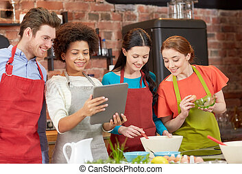 happy friends with tablet pc cooking in kitchen - cooking...