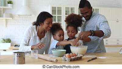 Happy full family having fun preparing pastry together at home.