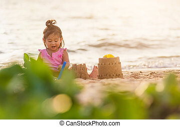 cute little girl playing sand with toy sand tools
