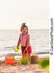 little girl playing sand with toy sand tools
