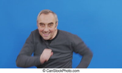 Happy fun mature man rejoices and dances isolated on blue background in studio. People emotions lifestyle concept