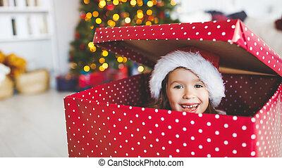 happy funny child girl hiding in big christmas present