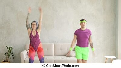 Happy funny couple doing jumping aerobic exercises at home in living room.