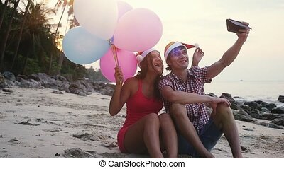 Happy funny couple sit on the beach with multicolored balloons on Christmas travel holidays taking selfie picture with smartphone wearing santa hat during beautiful sunset in slow motion.