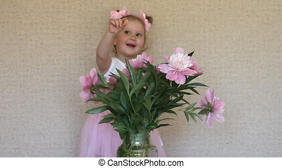 Happy funny little girl and a bouquet of peonies. The child is smiling and playing.