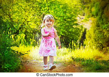 Happy funny little girl walking on road, nature outdoors