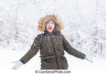 Happy funny male portrait looking snowflakes falling down