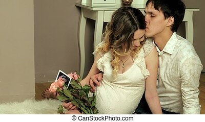 Happy future parents looking at pregnancy ultrasound photo -...