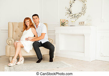Happy future parents sitting on the sofa