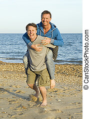 A happy smiling gay couple fooling around on the beach.