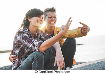 Happy gay couple dating on the beach at sunset - Young lesbians having fun enjoying time together outdoor - Lgbt, homosexuality love and relationhsip lifestyle concept