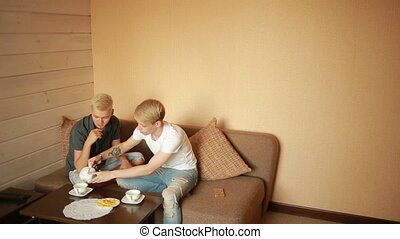 happy gay couple having breakfast on the couch. LGBT