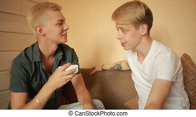 happy gay couple having breakfast on the couch. LGBT - happy...
