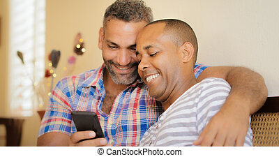 Happy Gay Couple Looking At Pictures On Mobile Phone