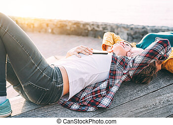 Happy gay couple lying next to the beach at sunset - Lesbian women having a tender romantic moment outdoor - Lgbt, homosexuality love and lifestyle relationship concept