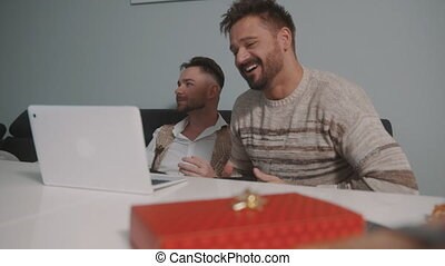 Happy gay couple or best friends playing video games. Gift in the foreground. High quality 4k footage