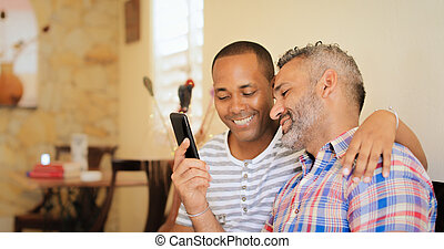 Happy Gay Couple Using Social Media On Mobile Phone