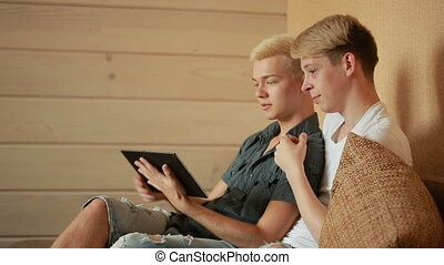 Happy gay couple using tablet in bed. gay couple. LGBT -...