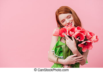 Happy ginger woman holding bouquet of flowers