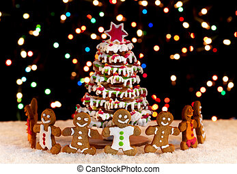 Happy gingerbread people around the christmas tree