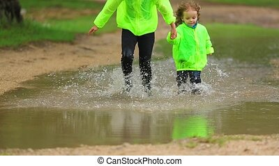 Happy Girl And Boy Having Fun In Huge Puddle