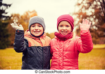 happy girl and boy waving hands in autumn park