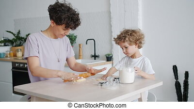 Happy girl and little son rolling dough making cookies at...