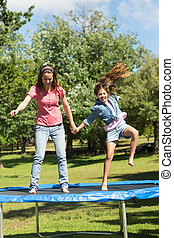 Happy girl and mother jumping high on trampoline in park