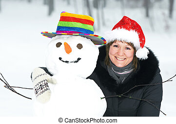 happy girl and snowman in winter