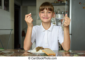 Happy girl at the dinner table holds a pill in one hand, a glass of water in the other