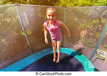 Happy girl bouncing up on the trampoline outdoors