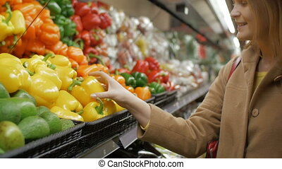 Slow motion clip of of a young smiling woman choosing fresh vegetables in the store. She taking some yellow peppers