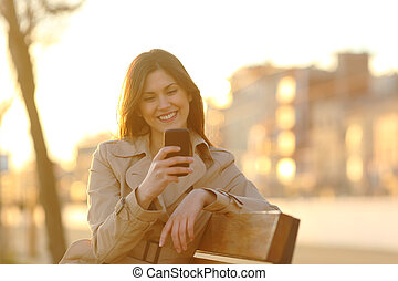 Happy girl checking smart phone at sunset on a bench