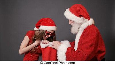 Happy Girl Chooses Gift in Santa's Bag