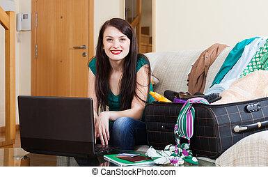 Happy girl choosing the resort on the internet