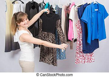 Happy girl chose a dress in the wardrobe